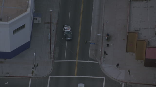 aerial. looking down on police station. police car emerges from station onto city street. driving toward camera. camera follows as it drives through city. shot in slow motion - police car stock videos & royalty-free footage
