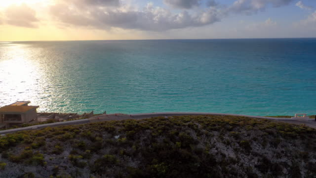 vidéos et rushes de aerial: looking over hill at serene tropical water during sunset - providenciales, turks and caicos - hill