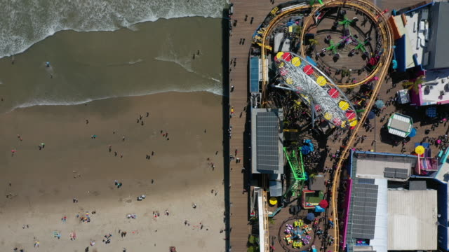 vídeos de stock e filmes b-roll de aerial: looking straight down at colorful amusement rides on santa monica pier and beachfront tourists - santa monica, california - santa monica