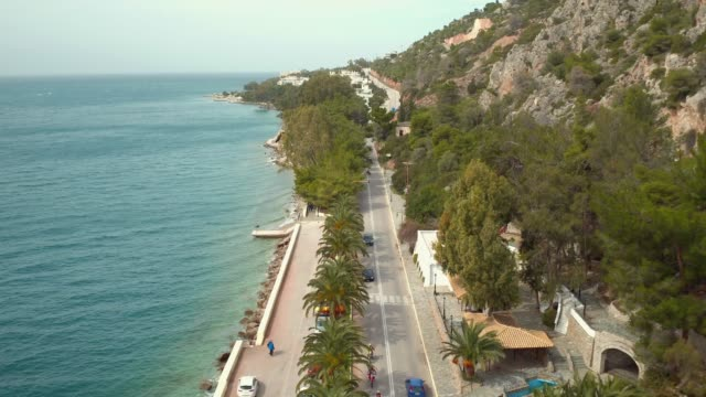 Aerial - Loutraki - Greece, backward flight and reveal of a coastal road with palm trees and a waterfall