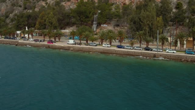 Aerial - Loutraki - Greece, backward revealing of a coastal road with palm trees and a waterfall