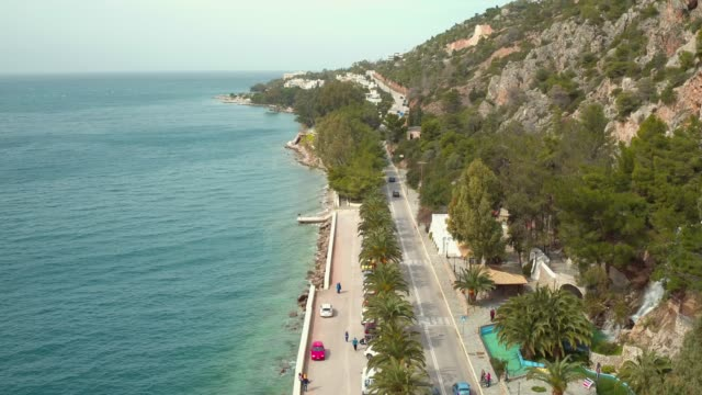 Aerial - Loutraki - Greece, steady shot from above of a coastal road with palm trees and a waterfall