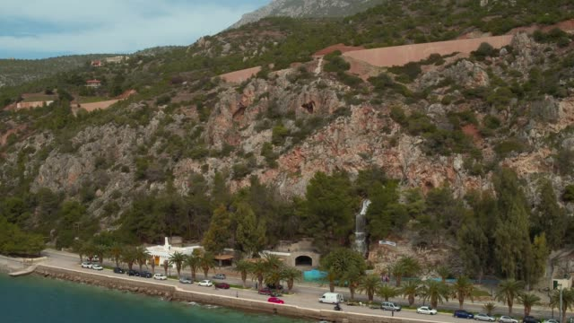 Aerial - Loutraki - Greece, vertical downward revealing of a coastal road with palm trees and a waterfall