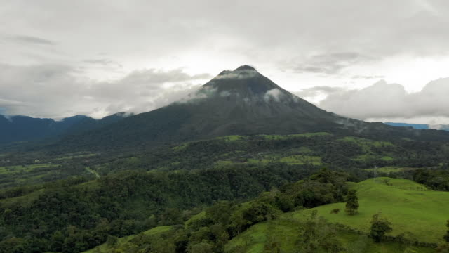 aerial: low clouds around lush green arenal volcano mountain - costa rica stock videos & royalty-free footage