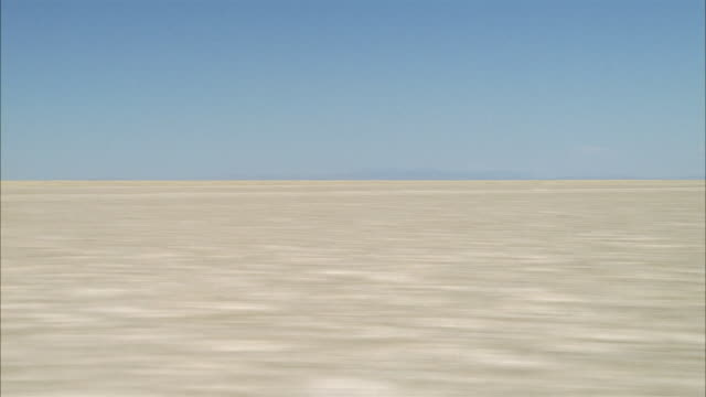 aerial low over dry lake bed and salt flats with hills in background / southwest usa - lake bed stock videos & royalty-free footage