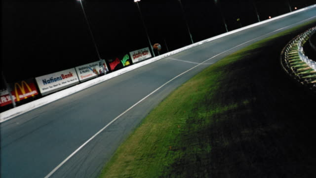 aerial low over empty superspeedway at charlotte motor speedway / night / concord, north carolina - sportstrecke stock-videos und b-roll-filmmaterial