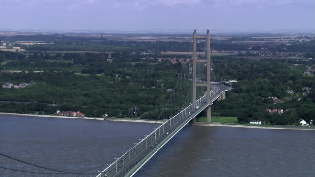aerial low over humber bridge over estuary / east riding, england - hull stock videos & royalty-free footage