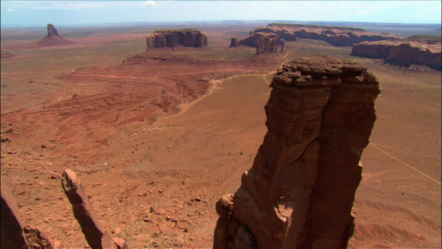 vidéos et rushes de aerial low over 'three sisters' rock formation / monument valley - piton rocheux