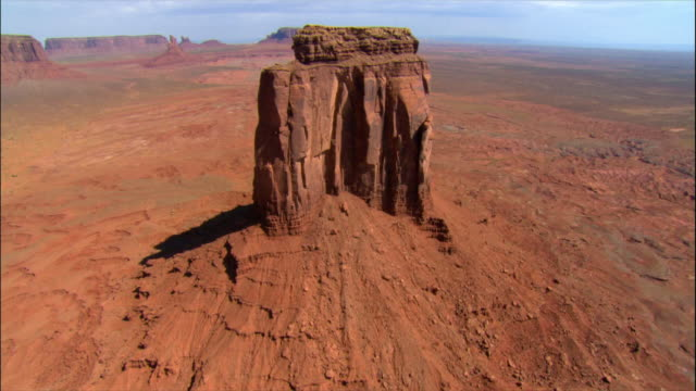 aerial low over top of east mitten butte / monument valley - butte rocky outcrop stock videos & royalty-free footage