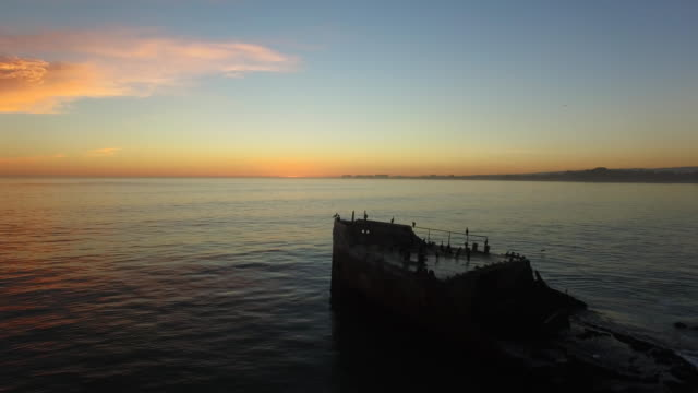 aerial low pan right: 4k uhd front of the cement ship at sunset - shipwreck stock videos & royalty-free footage