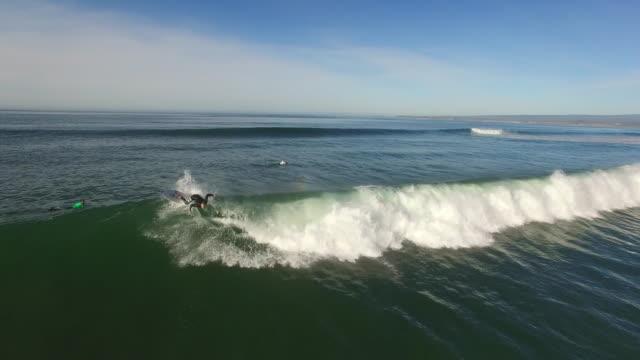 aerial low track: surfer cutbacks 4k uhd - サーフィン点の映像素材/bロール