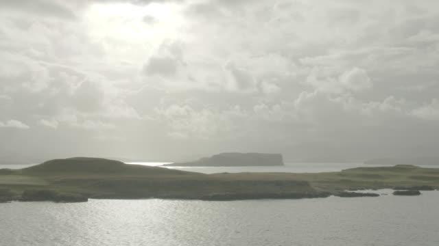 vidéos et rushes de aerial l-r over green grass, ocean and rocky cliffs; isle of skye, scotland, uk - îles hébrides
