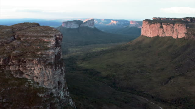 aerial: lush green valley among amazing mountains at dawn in chapada, brazil - canyon stock videos & royalty-free footage