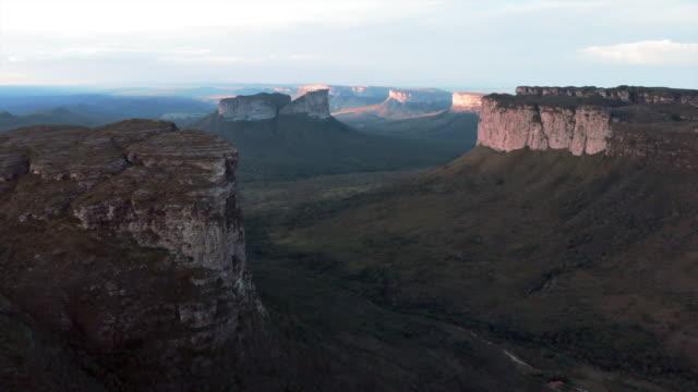 vídeos de stock, filmes e b-roll de aerial: lush green valley among amazing mountains in chapada, brazil - desfiladeiro