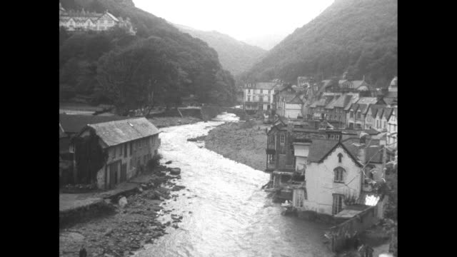 aerial lynmouth, small town in devon area of england, in aftermath of flash flood, with damaged buildings, debris / vs water rushes past pile of... - carefree stock videos & royalty-free footage