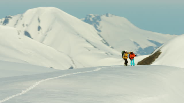 Aerial male female climbers on Alaska mountain snow