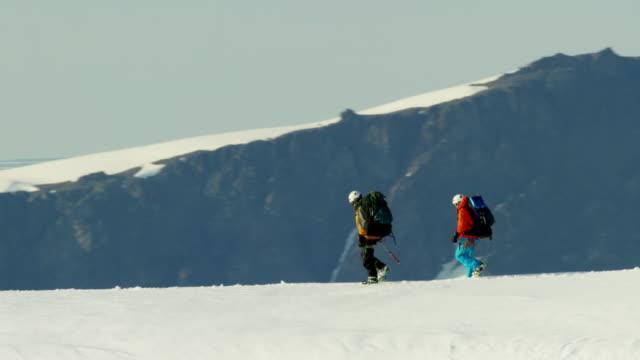 Aerial male female climbers on Alaska mountain snow