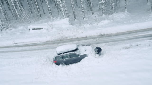 Aerial Man digging his car out of snow stuck by the road