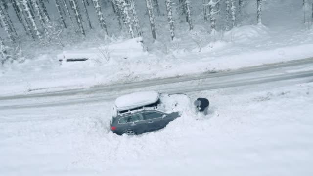 stockvideo's en b-roll-footage met luchtmens die zijn auto uit sneeuw graaft die door de weg wordt geplakt - klem