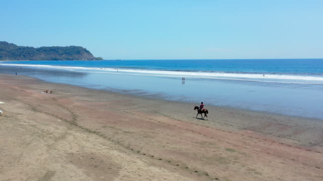aerial: man riding horse on empty beach near vibrant blue ocean and lush green hill in distance - jaco, costa rica - costa rica stock videos & royalty-free footage