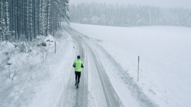 aerial man running in snowfall - country road stock videos & royalty-free footage
