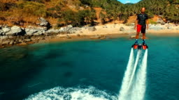 Aerial: Man standing over the water on flyboard near the beach.