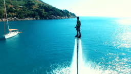 Aerial: Man standing over the water on flyboard.