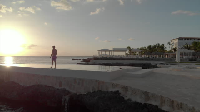 Aerial: Man Walking on the Edge of Swimming Pool next to the Ocean at Sunset