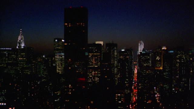 vídeos de stock e filmes b-roll de aerial manhattan skyline past chrysler building and empire state building at night - prédio chrysler