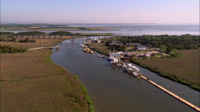 Aerial marshland and Savannah River/ fishing boats and village/ over motorway/ Cockspur Island Lighthouse/ Georgia