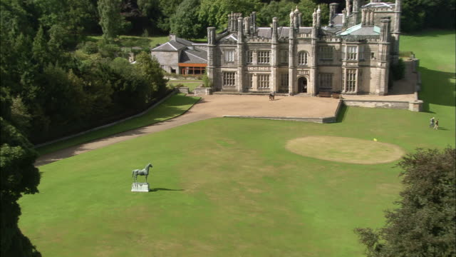 aerial medium shot bronze statue of stallion on grounds of dalmeny house / zoom out wide shot over mansion / scotland - royalty stock videos & royalty-free footage