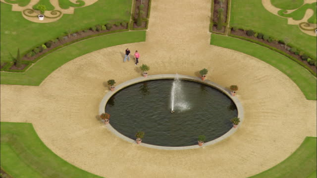 aerial medium shot couple walking around fountain in privy garden at hampton court palace / zoom out wide shot gardens, palace, and thames / surrey, england - surrey england stock videos & royalty-free footage