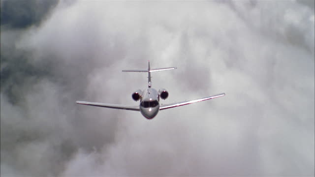 aerial medium shot front view private jet flying through clouds - air to air shot stock videos and b-roll footage