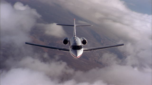 Aerial medium shot front view private jet in flight banking in air