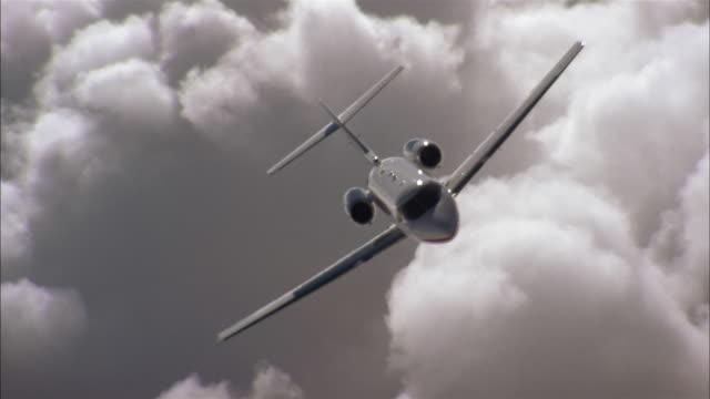 vídeos y material grabado en eventos de stock de aerial medium shot front view private jet in flight banking in air - toma aérea en vuelo