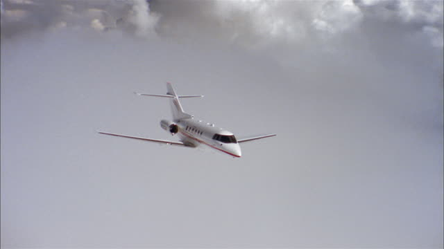 aerial medium shot private jet flying through clouds - private jet stock videos & royalty-free footage