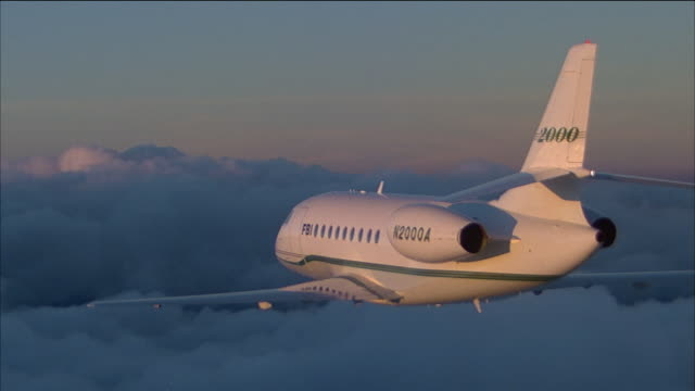 aerial medium shot rear view of a lear jet flying over thick clouds - air to air shot stock videos & royalty-free footage
