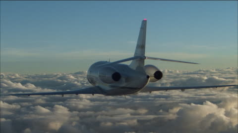 aerial medium shot rear view of lear jet flying over thick clouds / turning to the right - air to air shot stock videos & royalty-free footage
