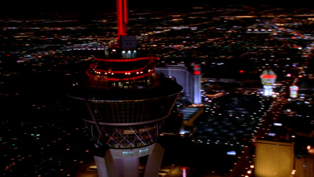 Aerial medium shot rotating around top of Stratosphere Tower at night with zoom in to casinos in background / Las Vegas