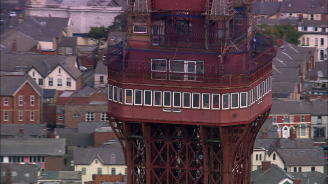 Aerial medium shot top of Blackpool Tower/ zoom out tower, coastline, and horizon/ Blackpool, England