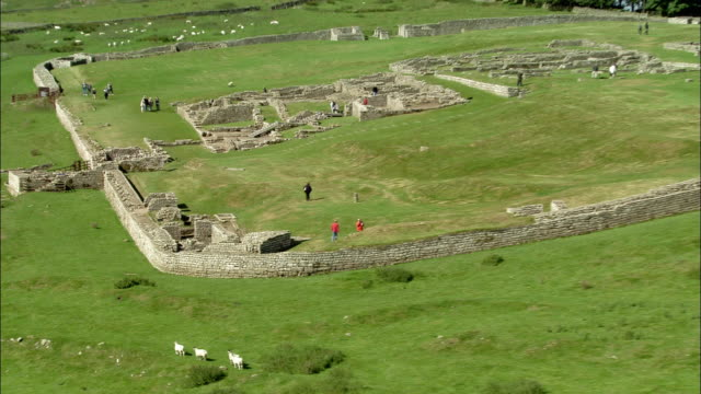 aerial medium shot wall of housteads roman fort / wide shot pull back to view of people visiting site / england - northumberland video stock e b–roll