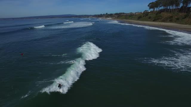 aerial medium tilt down track: surfer cutbacks 4k uhd - カリフォルニア州サンタクルーズ点の映像素材/bロール