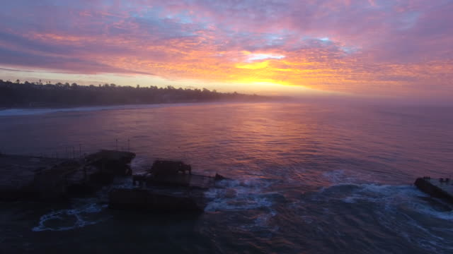 aerial medium track right: 4k uhd shipwreck sunrise - pacific ocean点の映像素材/bロール