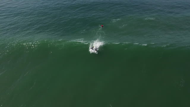 Aerial Medium Track: Surfer catching & riding a wave 4K UHD