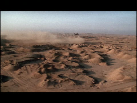 Aerial military helicopter flying over desert with dust cloud below/ Kuwait