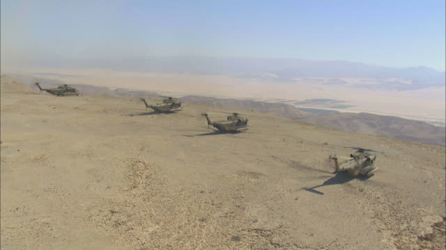 aerial military helicopters on cliff in desert, arava, israel - israelisches militär stock-videos und b-roll-filmmaterial