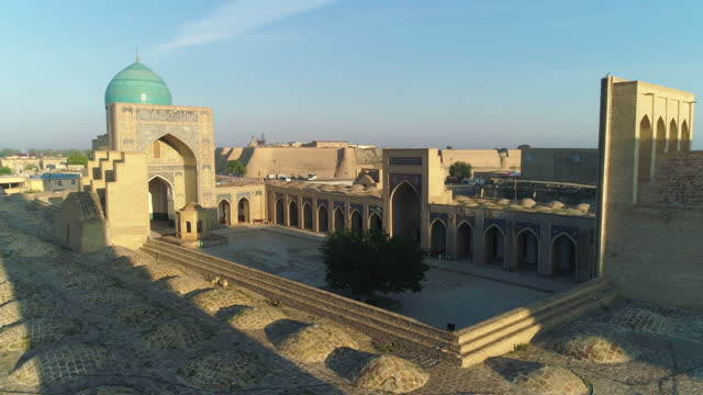 aerial: mir-i-arab madrasa amidst surrounding wall on sunny day clear sky - bukhara, uzbekistan - minaret stock videos & royalty-free footage