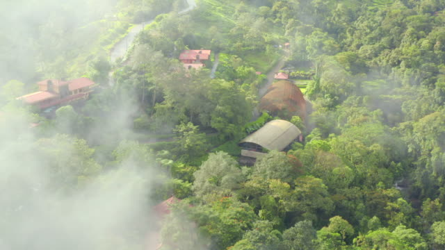 aerial: mist over houses among lush green - costa rica stock videos & royalty-free footage