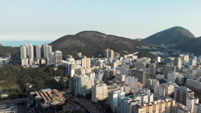 vídeos de stock, filmes e b-roll de aerial: modern city and road among scenic mountains - centro da cidade