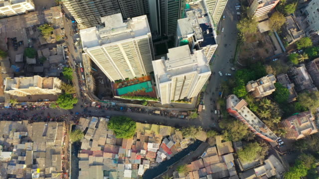 aerial: modern residential skyscrapers by slum in city - mumbai, india - slum stock-videos und b-roll-filmmaterial